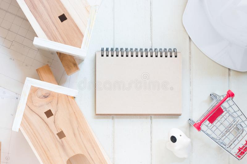 Blank paper notebook with Miniature house model. Blueprint plan, red cart and white safety helmet on white wood background, financial concept stock photos