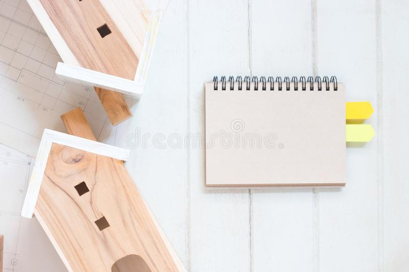 Blank paper notebook with Miniature house model and blueprint plan. On white wood background stock photography