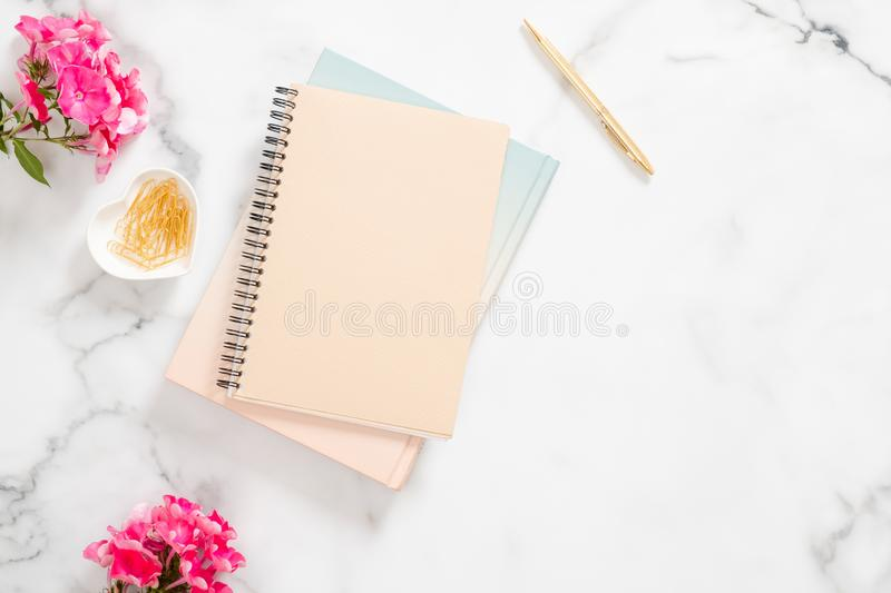 Blank paper notebook, pink flowers, golden stationery on marble background. Flat lay, top view feminine home office desk stock image