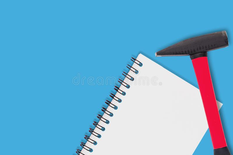 Blank paper notebook with spiral holder near hard metal hammer lies on blue table in workroom. Top view royalty free stock photography