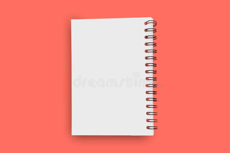 Blank paper notepad with spiral wire for note or drawing in center on background of living coral color. Copy space for your text. Business or education or stock photos
