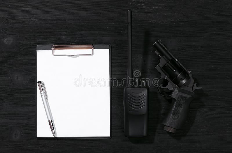 Security. Blank paper page, pen, portable radio station and handgun on a black background. Top secret document mockup. Detective agent dossier. Interrogation stock images