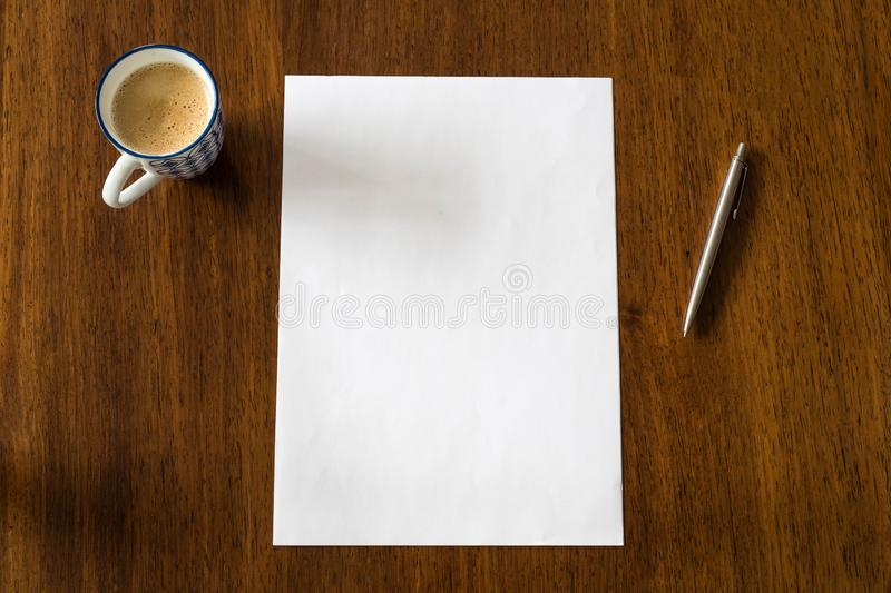 Blank paper with pen and coffee cup on wood table, space for text royalty free stock photography