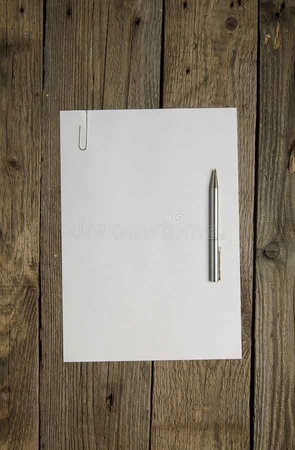 Blank paper and pen on dark wood background. Above view royalty free stock photos