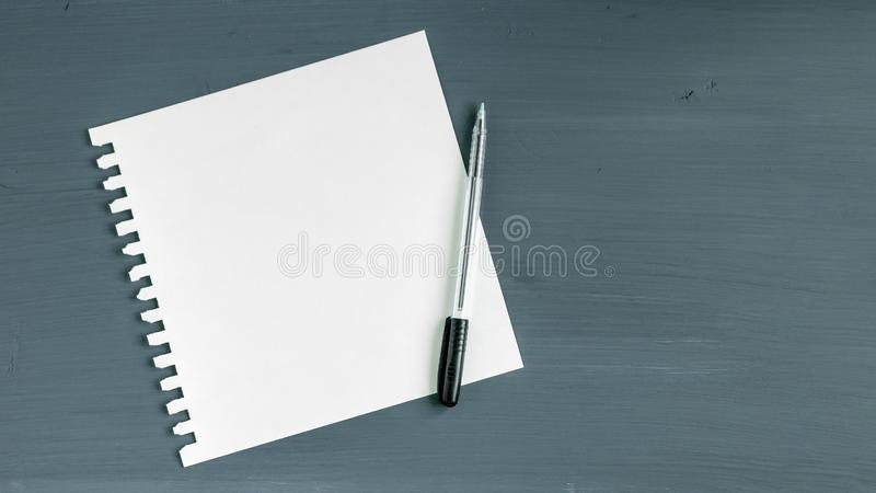 Blank paper and pen on grey wooden background stock image