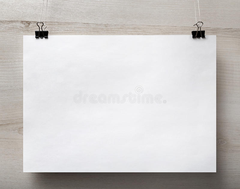 Blank paper poster. Blank white paper poster hanging on light wooden background. For design presentations and portfolios. Front view royalty free stock photo