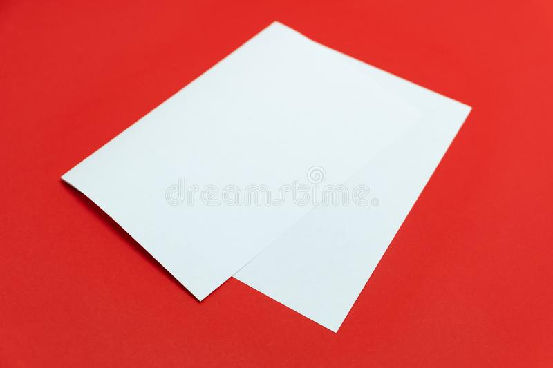Blank paper sheet on bright red background. Close-up view of bent white paper laying on vivid colored table top stock image