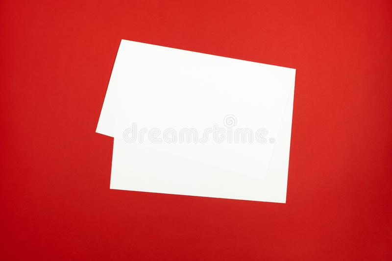 Blank paper sheet on bright red background. Top view of bent white paper laying on vivid colored table top stock photography