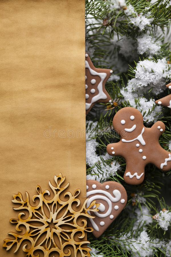 Paper sheet and Christmas gingerbread cookies on snow covered tree. Blank paper sheet and Christmas gingerbread cookies on snow covered spruce tree branches stock photos
