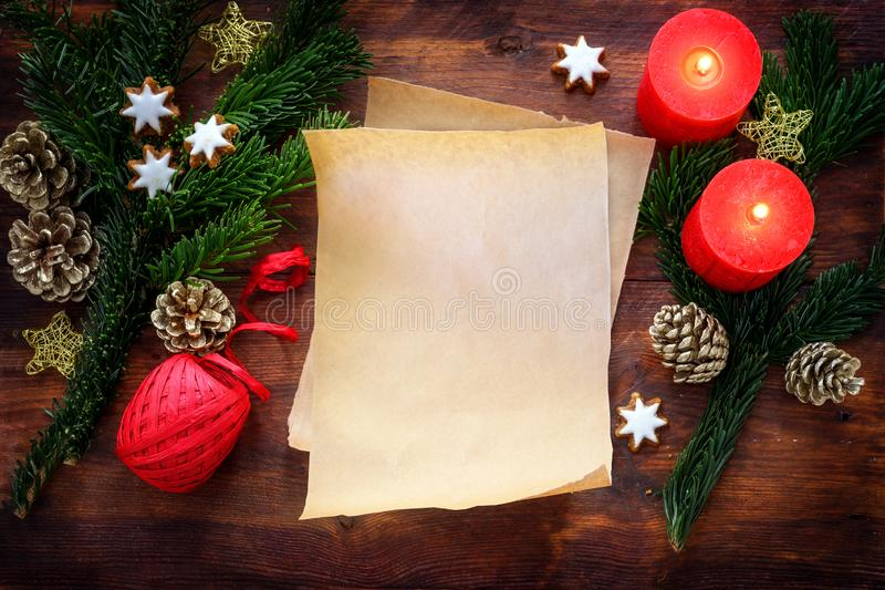 Blank paper sheet between fir branches, burning candles, cinnamon stars, cones and Christmas decoration on rustic dark wood, copy. Space, top view from above royalty free stock images