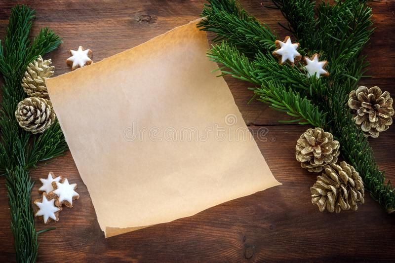 Blank paper sheet between fir branches, cinnamon stars and Christmas decoration for recipe, shopping list or a wish letter to. Santa Claus on a dark wooden stock image