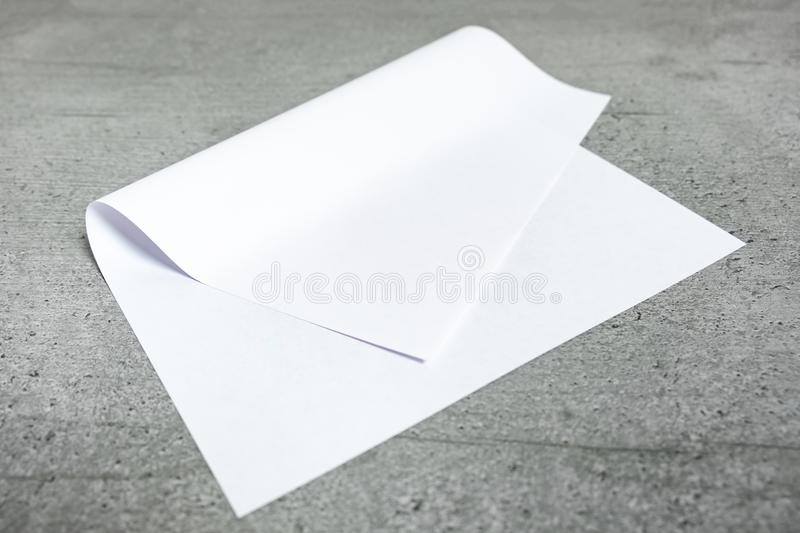 Blank paper sheet on grey background. Close-up view of bent white paper laying on cement stylised table top royalty free stock photos