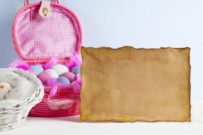 Blank paper sheet and pink basket full of colored eggs royalty free stock photos