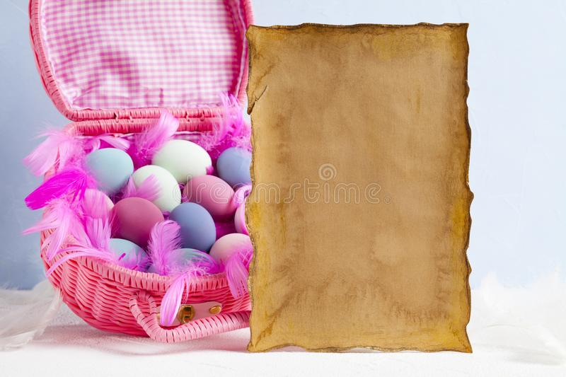 Blank paper sheet and pink basket full of colored eggs stock photo