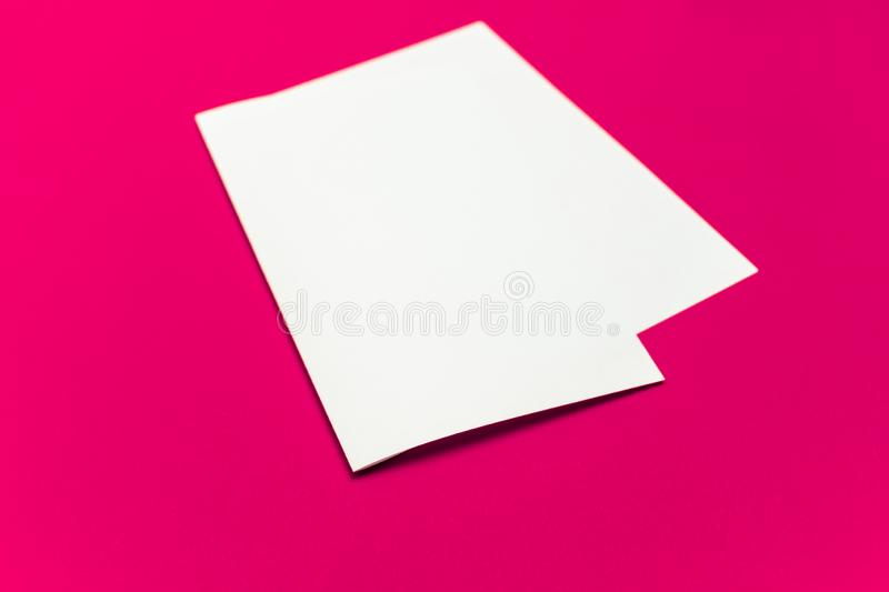 Blank paper sheet on `plastic pink` colored background. Close-up view of bent white paper laying on bright table top royalty free stock image