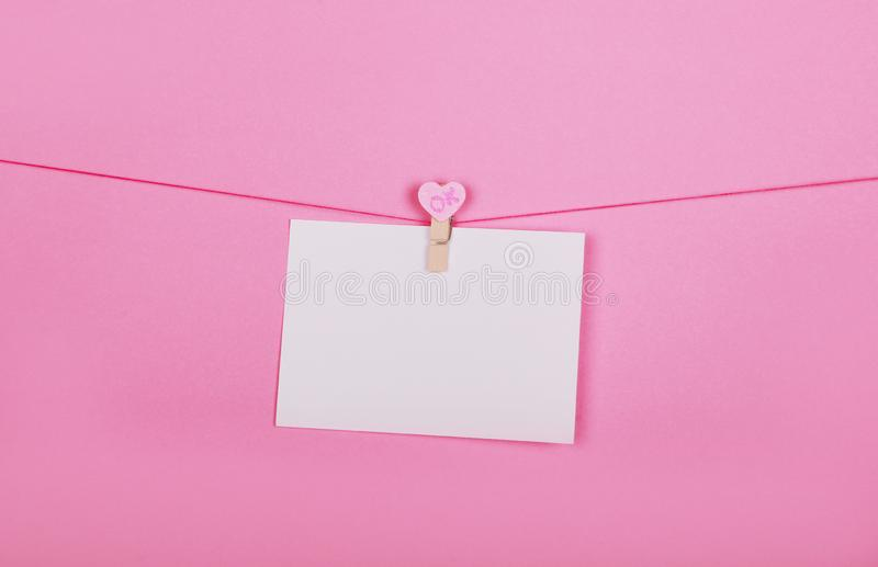 Blank paper sheets on a clothes line on a pink background. Pink hearts on clothespegs. Valentines day, Mother Day concept. royalty free stock photography