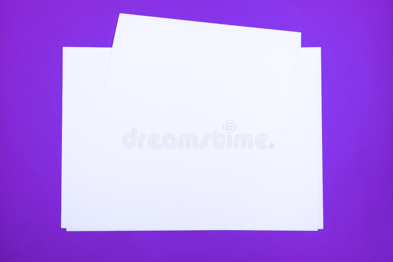 Blank paper sheets on `proton purple` background. Top view of white paper laying on bright colored table top royalty free stock images
