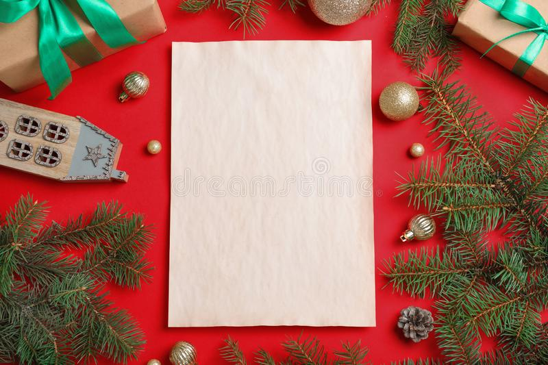Blank paper with space for text and Christmas decor on background, flat lay. Letter to Santa Claus. Blank paper with space for text and Christmas decor on red royalty free stock photo