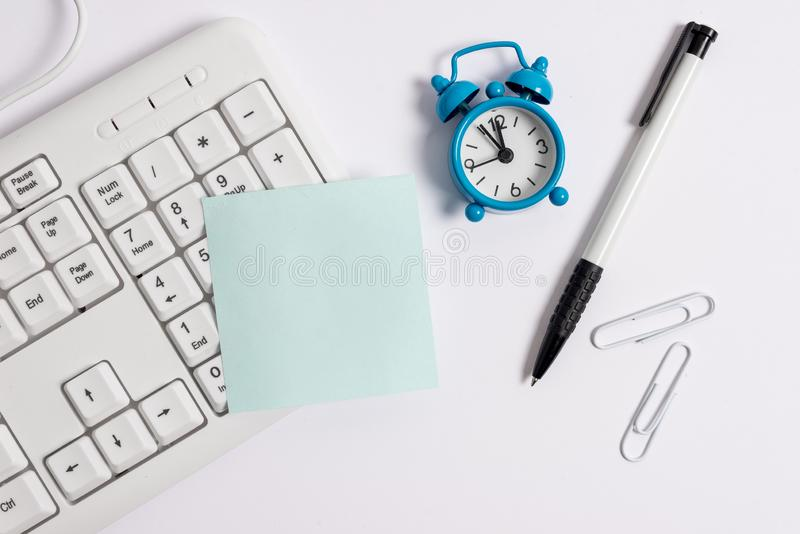 Blank paper space for textual message. White pc keyboard with empty note paper above white background. Business concept stock photography
