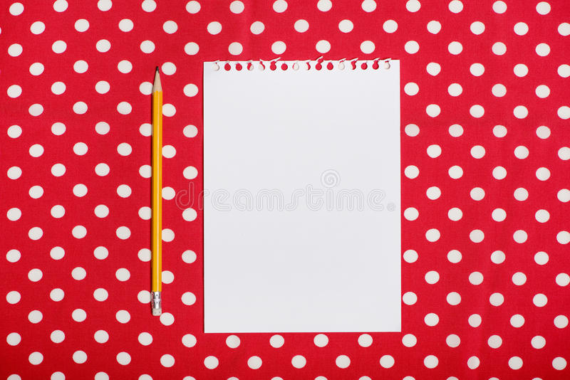 Blank parer and pencil on red and white surface. Top view of blank parer and pencil on red and white surface stock photography