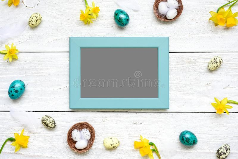 Blank photo card in frame made of quail eggs, spring flowers and feathers on white wooden background stock image