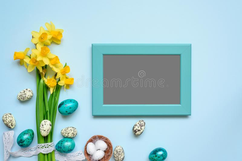 Blank photo frame with easter eggs and spring flowers mock up over blue background. top view royalty free stock image