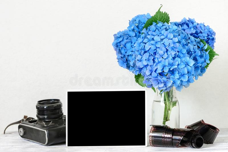 Blank photo frame and vintage retro camera with beautiful bouquet of blue hydrangea flowers and rolled film royalty free stock image