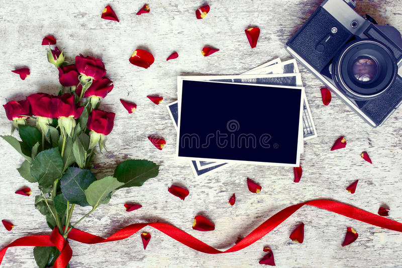 Blank photo frame, vintage retro camera and red roses royalty free stock photos