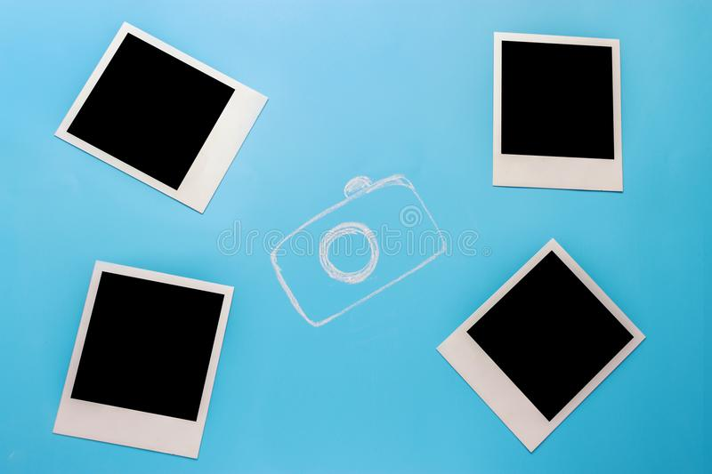 Blank photo frames, camera. On blue background royalty free stock photography