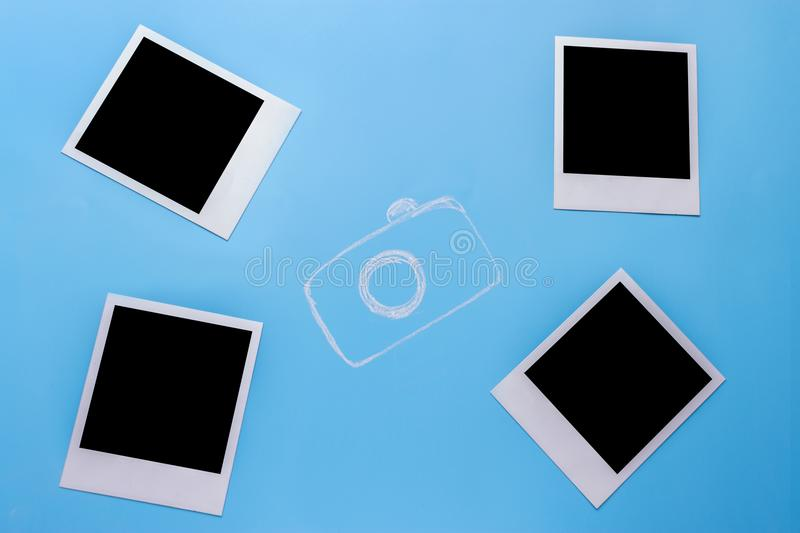 Blank photo frames, camera. On blue background stock photography