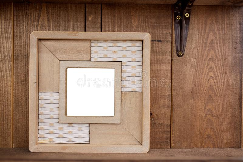 Blank photo frames and plant on shelf in front of wooden wall royalty free stock photo