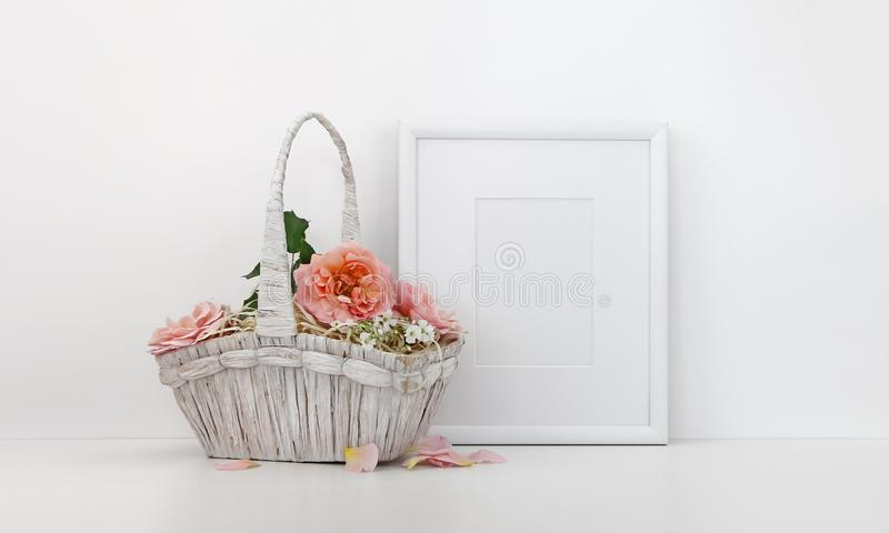 Blank picture frame mockup with a basket of roses stock photo