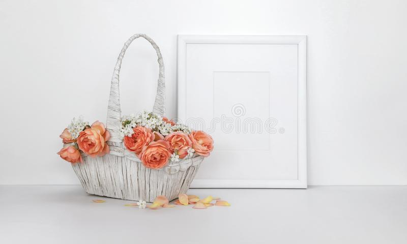 Blank picture frame mockup with a basket of roses stock photography
