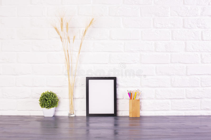 Blank picture frame. Pencil holder, plant and wheat spikes on wooden desktop and white brick wall background. Mock stock images