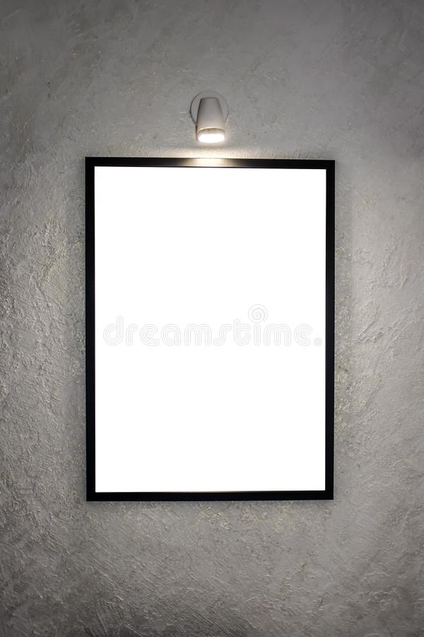 The picture in a black frame, hanging on the wall and illuminated by a lamp for paintings. On the background of a white stock photos