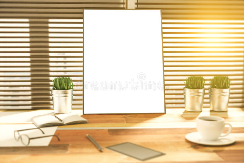 Blank picture frame on a wooden desk at sunset stock photo