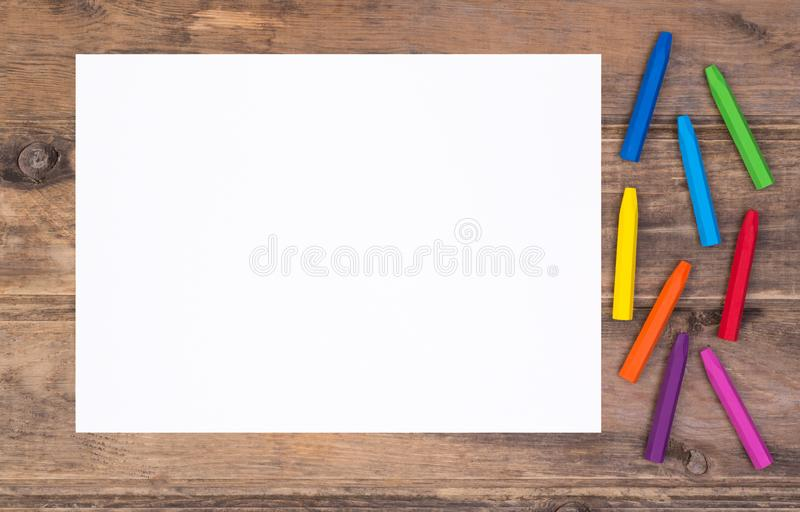 Blank piece of paper with colorful crayons on kid`s desk royalty free stock photos