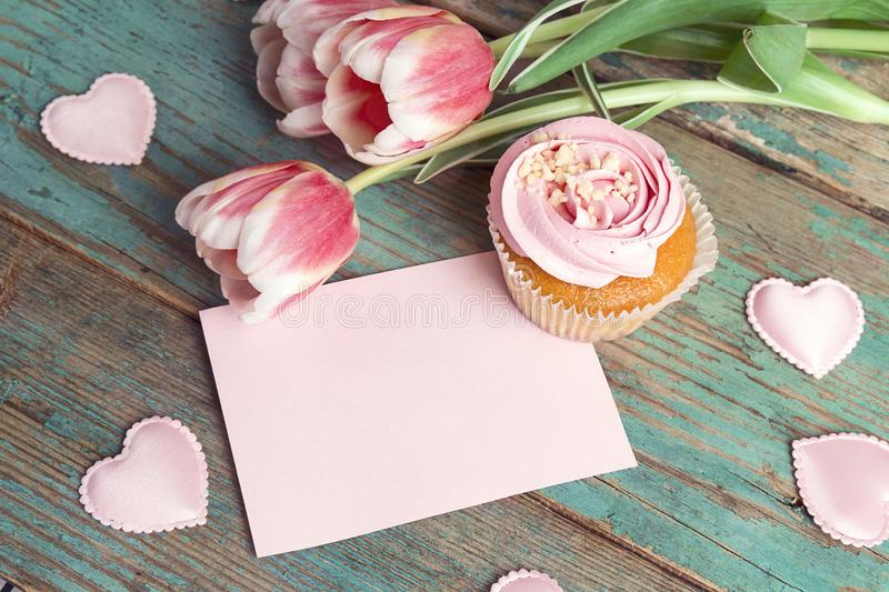 Blank pink card with cupcake, tulips and hearts on turquoise wooden background. Romantic love background stock image