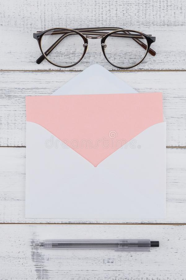 Blank pink card in white envelop, eyeglasses stock photo
