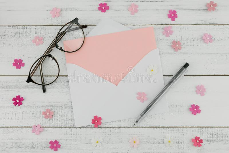 Blank pink card in white envelope, pen and eyeglasses. Decorate with pink paper flowers on white wood background with copy space stock photo