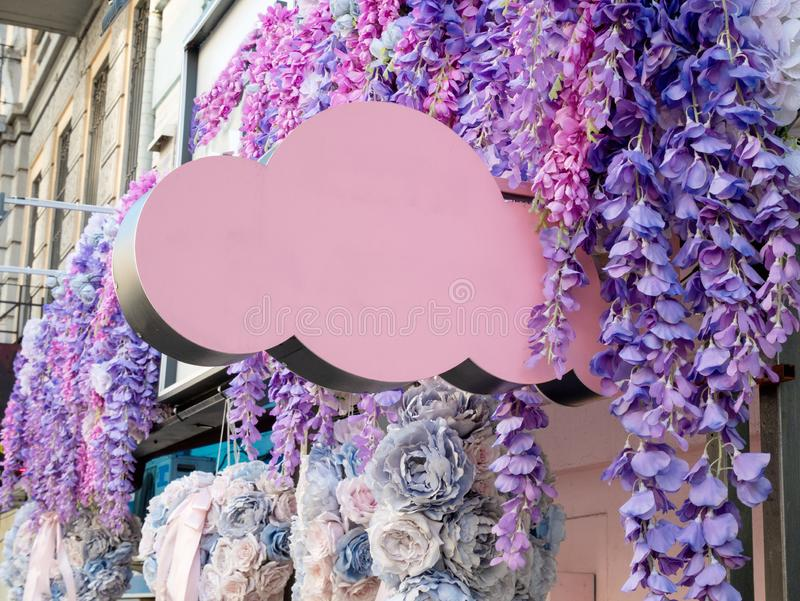Blank pink color signboard in shape of a cloud with hanging flowers around. beauty, spa or wedding salon, flower shop concept stock photos