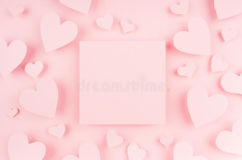 Blank pink square page with paper hearts on light background. Advertising concept for Valentine day. stock images