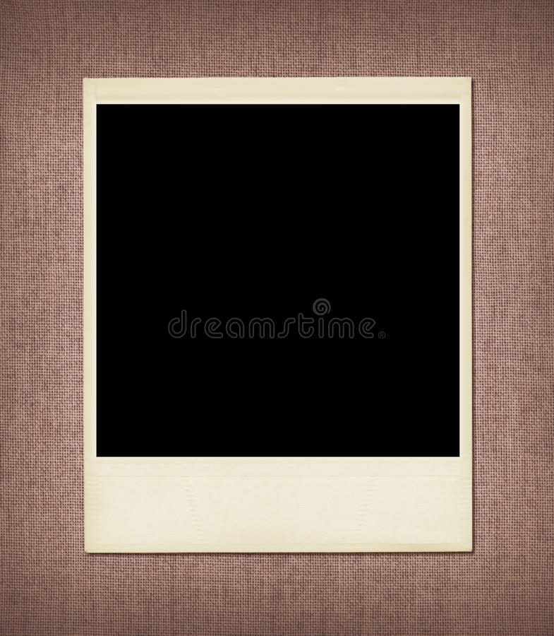 Blank Polaroid Frame. Blank undeveloped polaroid instant film as a frame on woven fabric background stock image