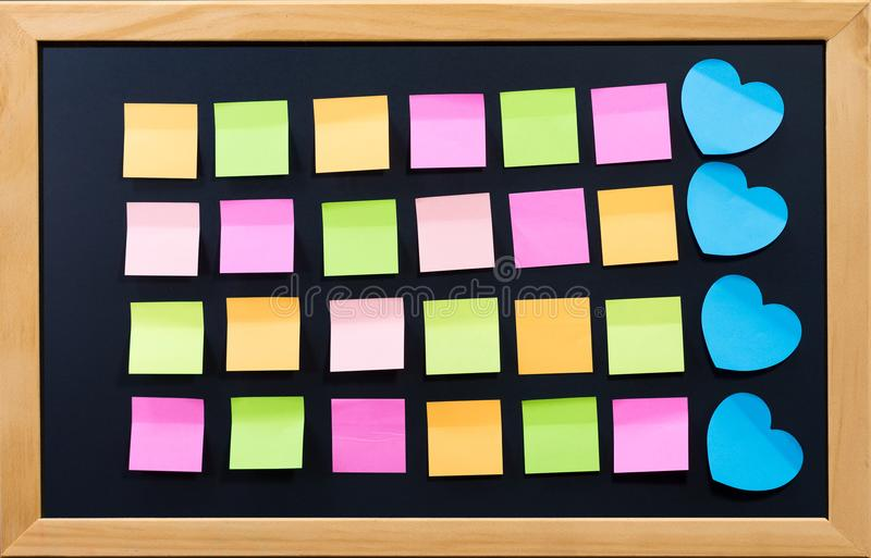 Blank post it on black board for memo or business. royalty free stock photography