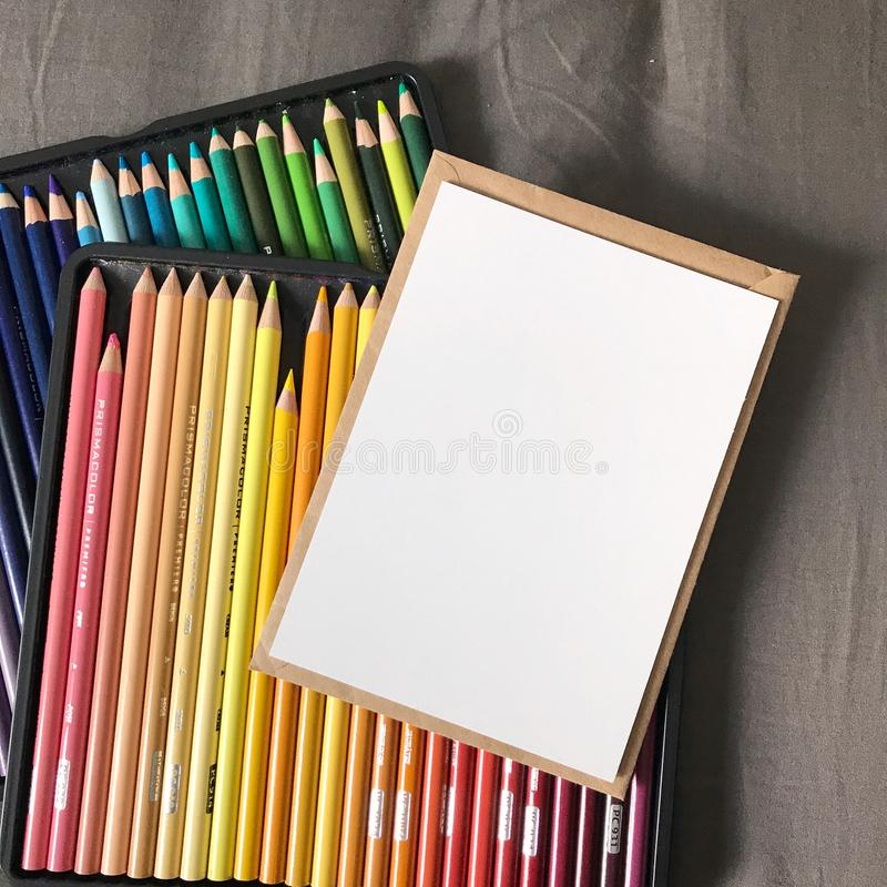 Blank Postcard with Envelope and Colored Pencils. Blank post card with brown kraft paper envelope and colored pencils in packaging. Perfect as product mock up royalty free stock photo