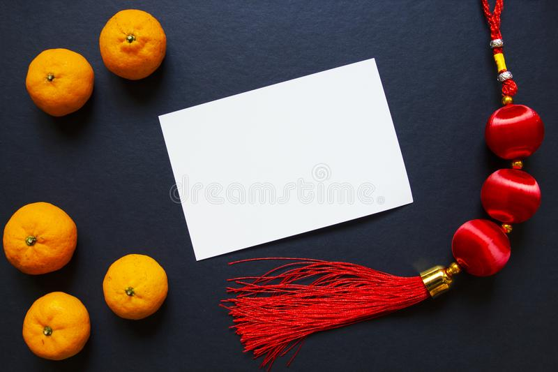 Blank postcard with Chinese new year tassel and tangerines on black background. Lunar New Year top view photo. Oriental lucky knot. Asian winter holiday royalty free stock photography