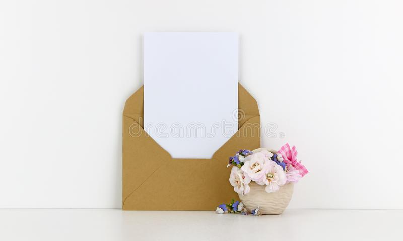 Blank postcard mockup with craft paper envelope and white flowers. White background royalty free stock images
