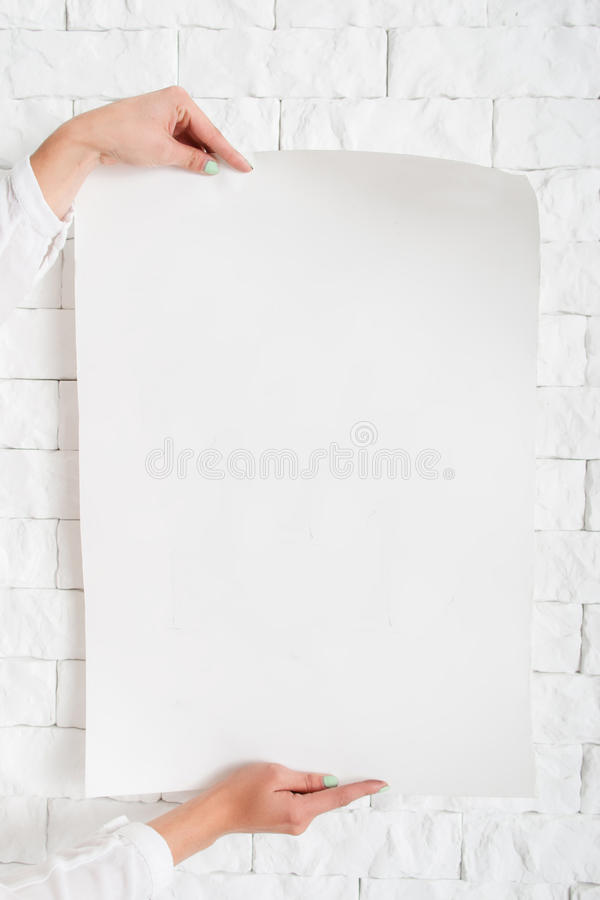 Blank poster in female hands against wall mockup. Close-up of woman holding empty sheet of paper with free space for text, advertisement, promo, warning stock image