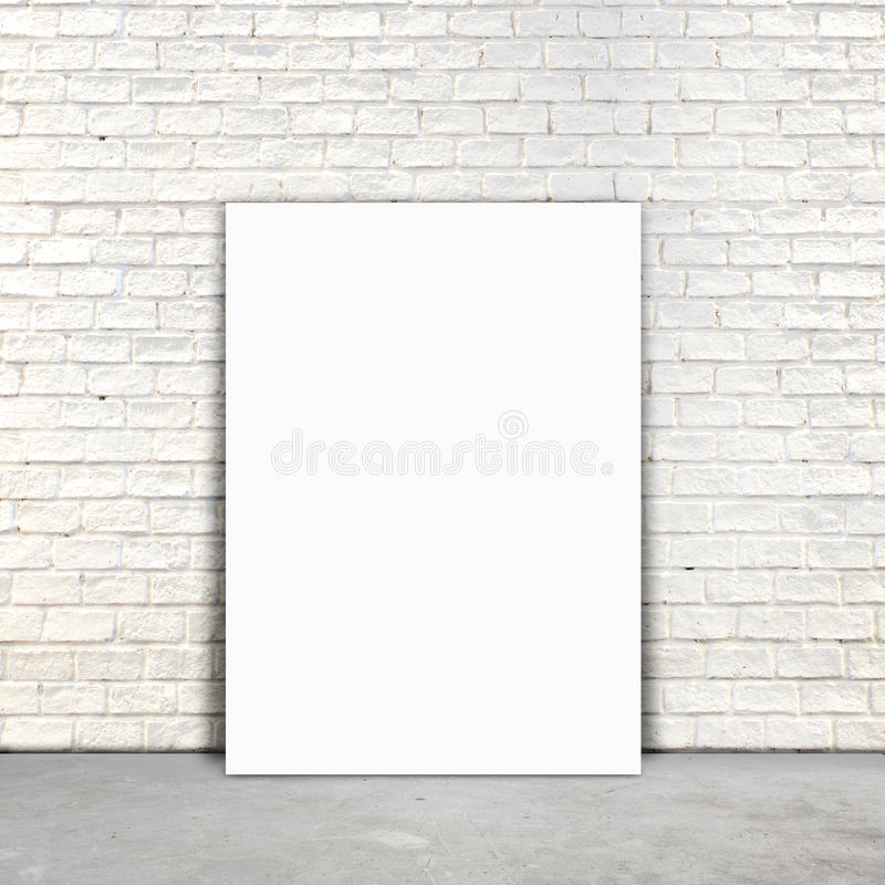 Blank Poster paper standing next to a white brick wall royalty free stock images