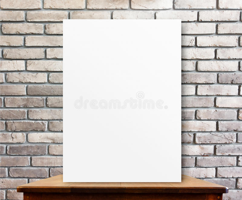 Blank poster on wood table at brick wall,perspective background.  royalty free stock photo